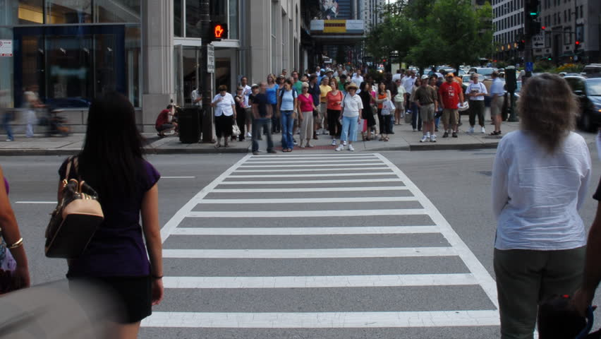 Crowds crossing urban street time lapse
