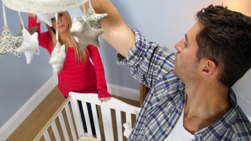 Couple expecting baby hang mobile over cot in newly decorated nursery. Shot on Sony FS700 at a frame rate of 25fps