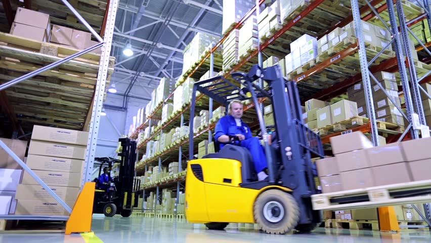 Forklift trucks move between large metal shelves at a modern warehouse and unload pallets with cardboard boxes