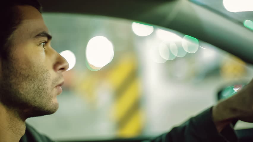 A man driving the car at undergroung parking. Close up. Bokeh background