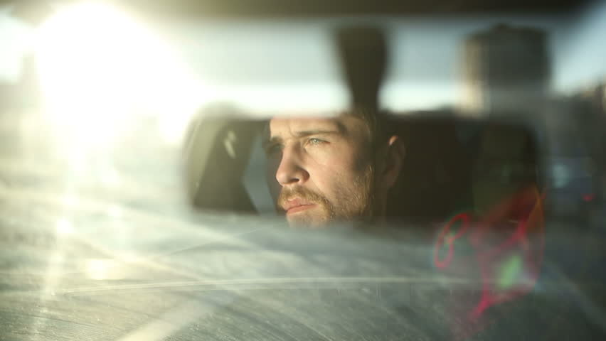 Man is driving a car. Reflection face in rearview mirror of vehicle. Time of sunset in a city