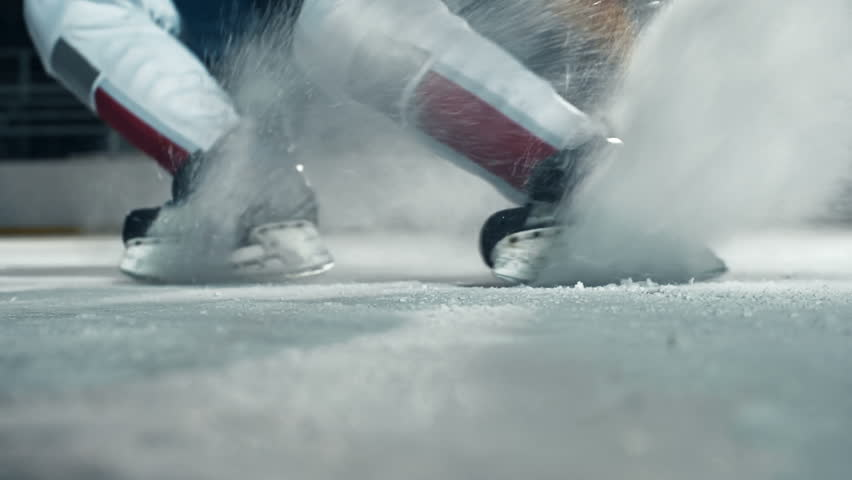 Low angle of hockey player running towards camera on skates and doing a turn cutting ice to powder   Shutterstock Video #9344261