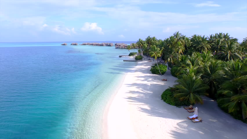 AERIAL: Luxury island resort on exotic white sand beach