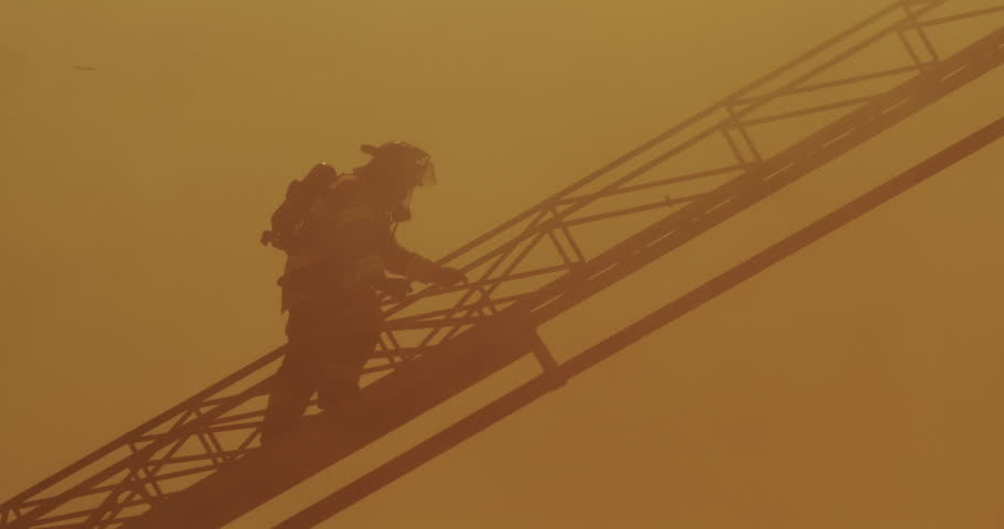Fireman with self-contained breathing apparatus climbing aerial ladder through thick heavy smoke above fire