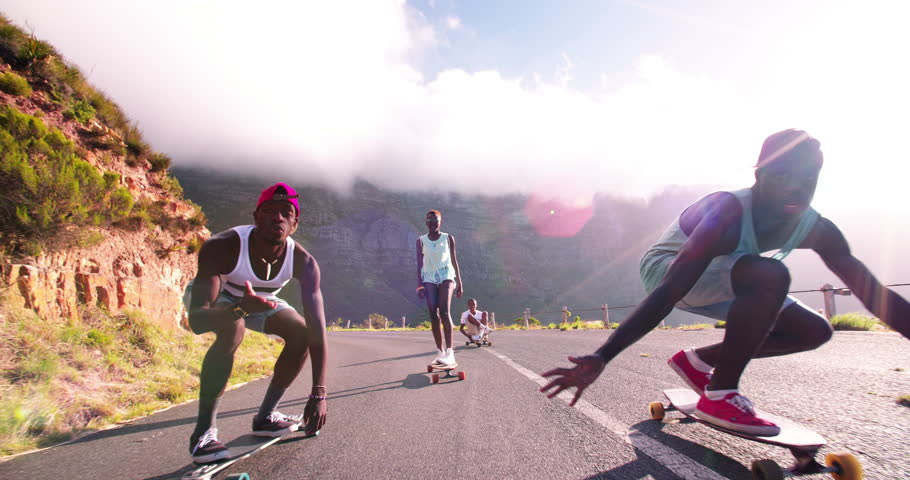 Mixed group of teenaged longboarders racing each other downhill on a mountain road in Slow Motion | Shutterstock Video #9517112