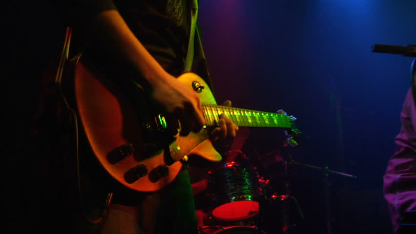 This is a close up shot of a man playing a guitar at a rock concert at a popular