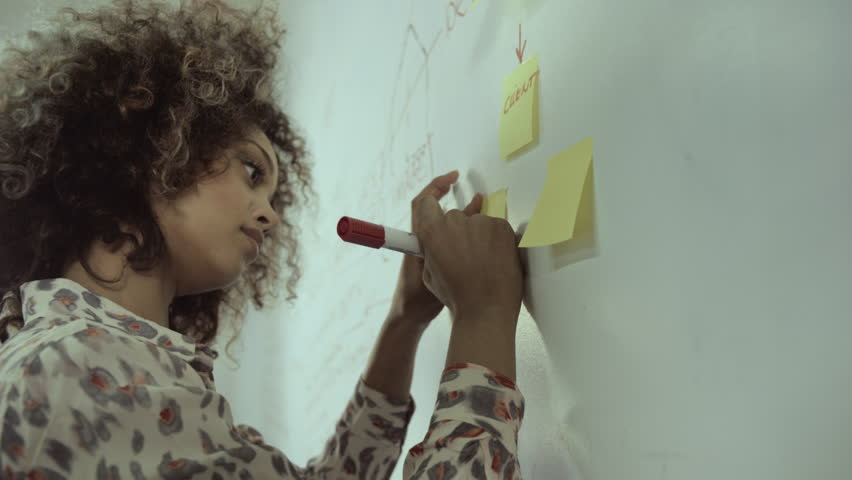 Young woman writing on adhesive note in office