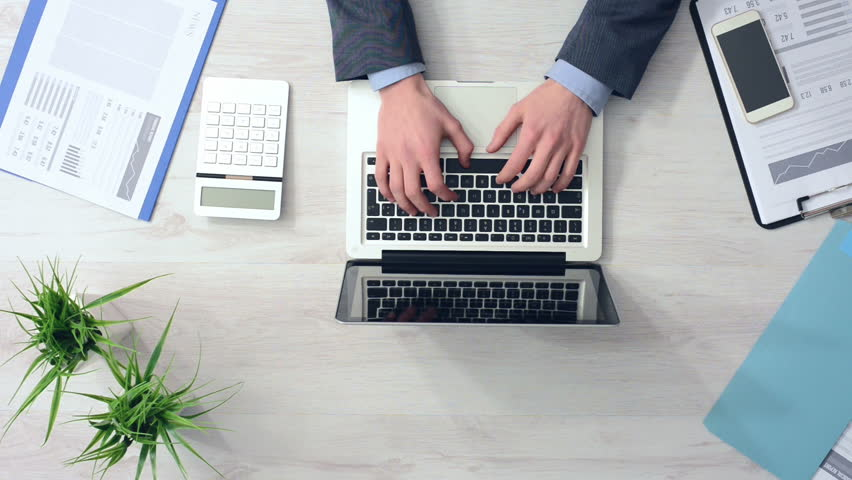 Professional businessman working at office desk with his laptop and financial reports, hands top view