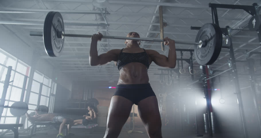 Medium shot slow mo tilt-down tilt-up men and women exercising and lifting weights female bodybuilder champion athlete doing power clean in cross fit gym