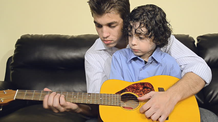 Elder brother teaching his sibling how to play guitar, family spending quality time together in non technological recreation
