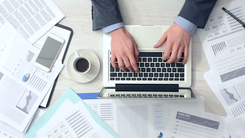 Businessman working at office desk with his laptop and drinking coffee surrounded by a lot of paperwork and financial reports, hands top view